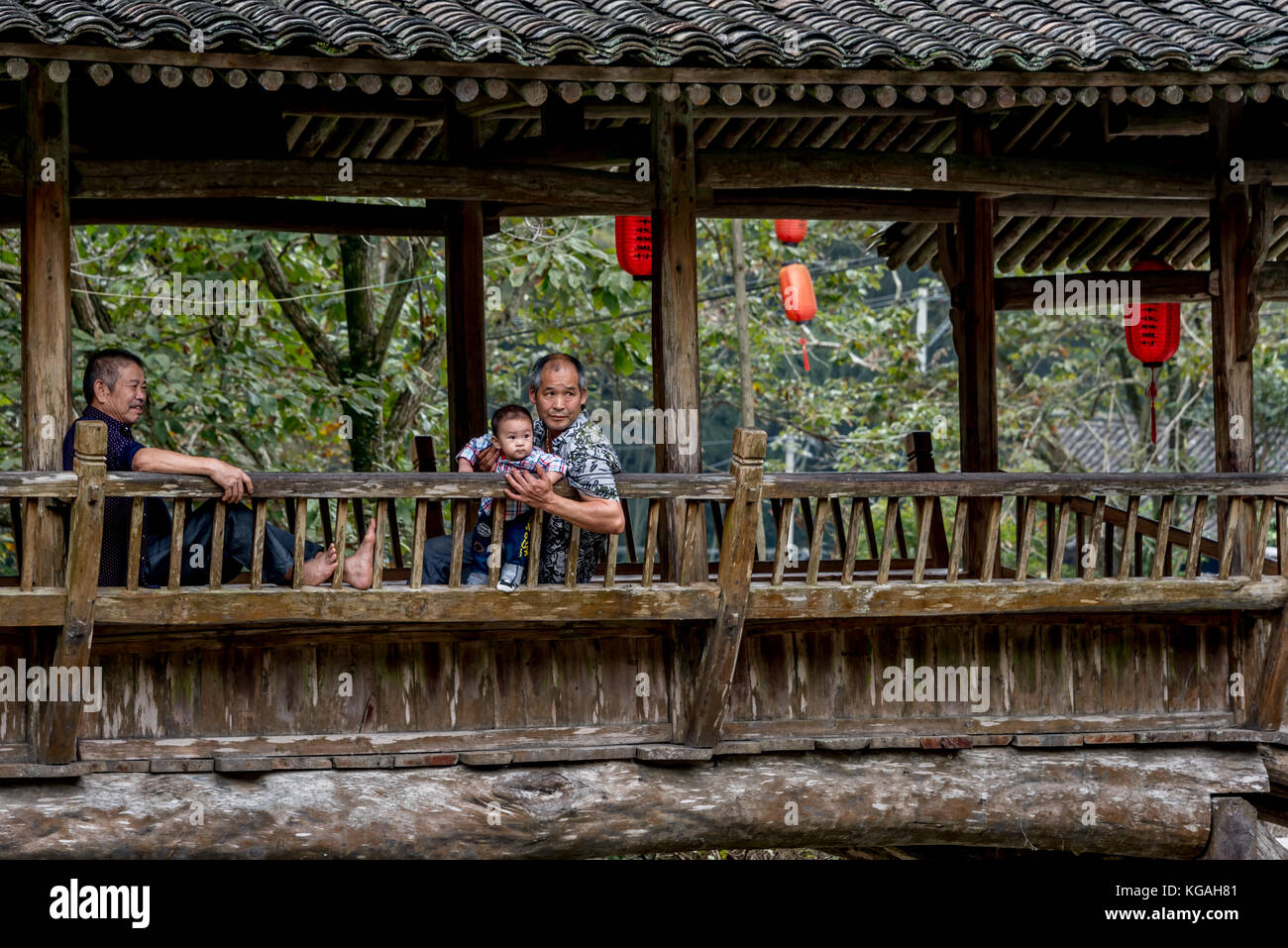 Chinese grandfathers or older men keep cool on the covered bridge with baby boy in Lingshang Renjia or Linkeng ancient - Stock Image