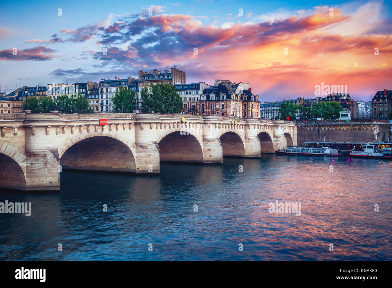 Famous Pont Neuf in Paris, France. Spectacular cityscape with dramatic sunset sky. Travel and architectural background. - Stock Image
