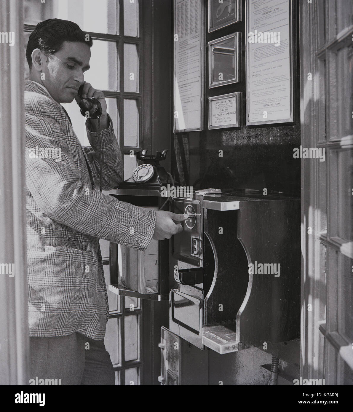 Early 1950s, historical picture showing an overseas male visitor to England making a call from a public telephone - Stock Image