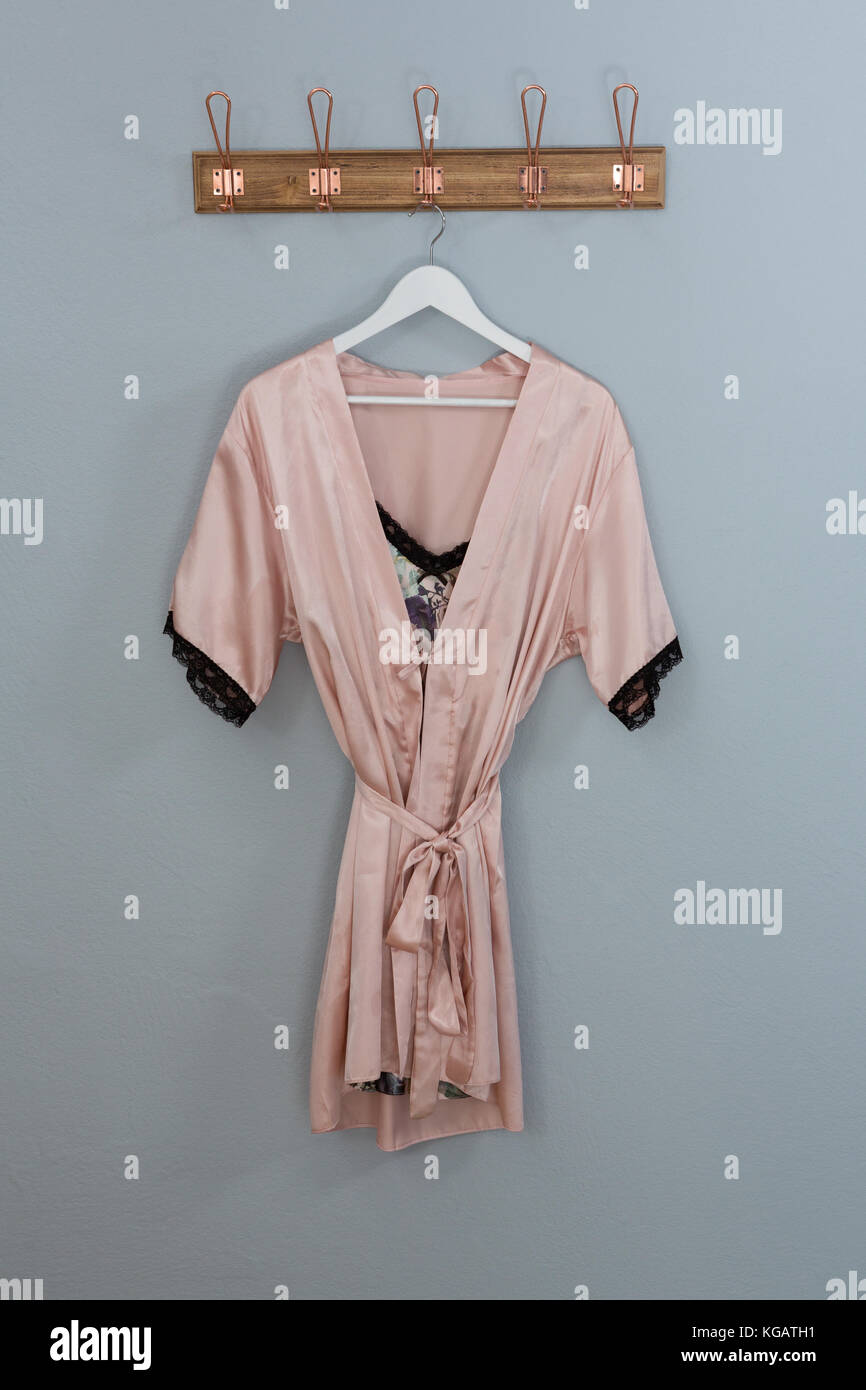 Nightwear hanging on hook against wall - Stock Image