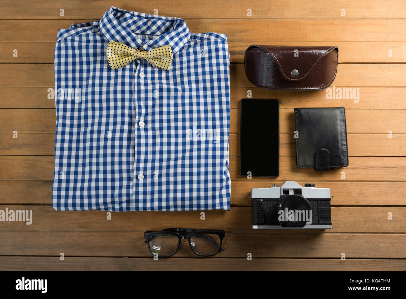 Folded shirt, spectacle, camera, wallet, and mobile phone arranged on wooden plank - Stock Image