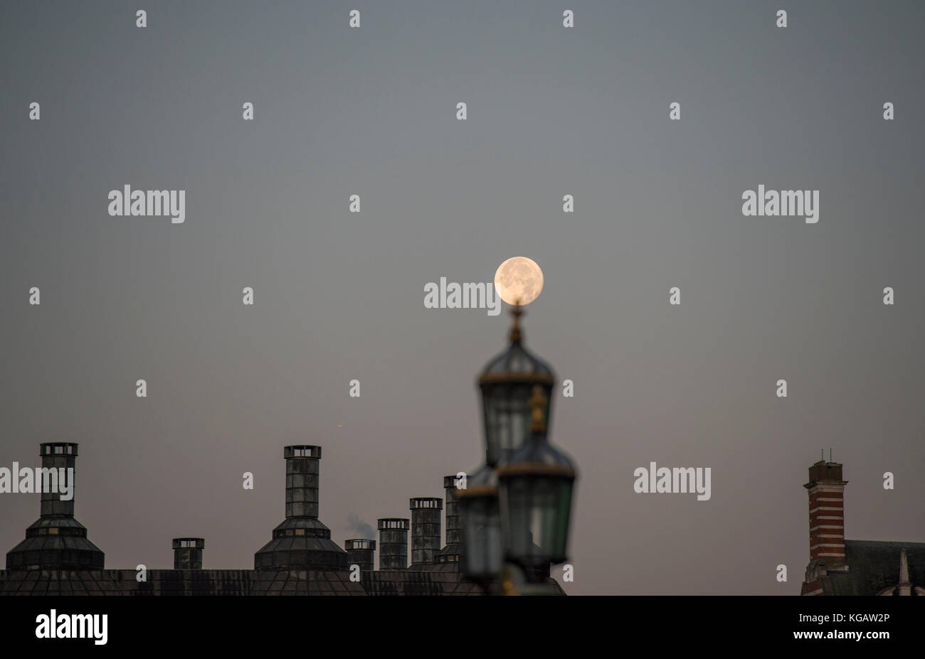 The moon above Portcullis House and Old Scotland Yard at sunrise in Autumn with street lamp on Westminster Bridge - Stock Image