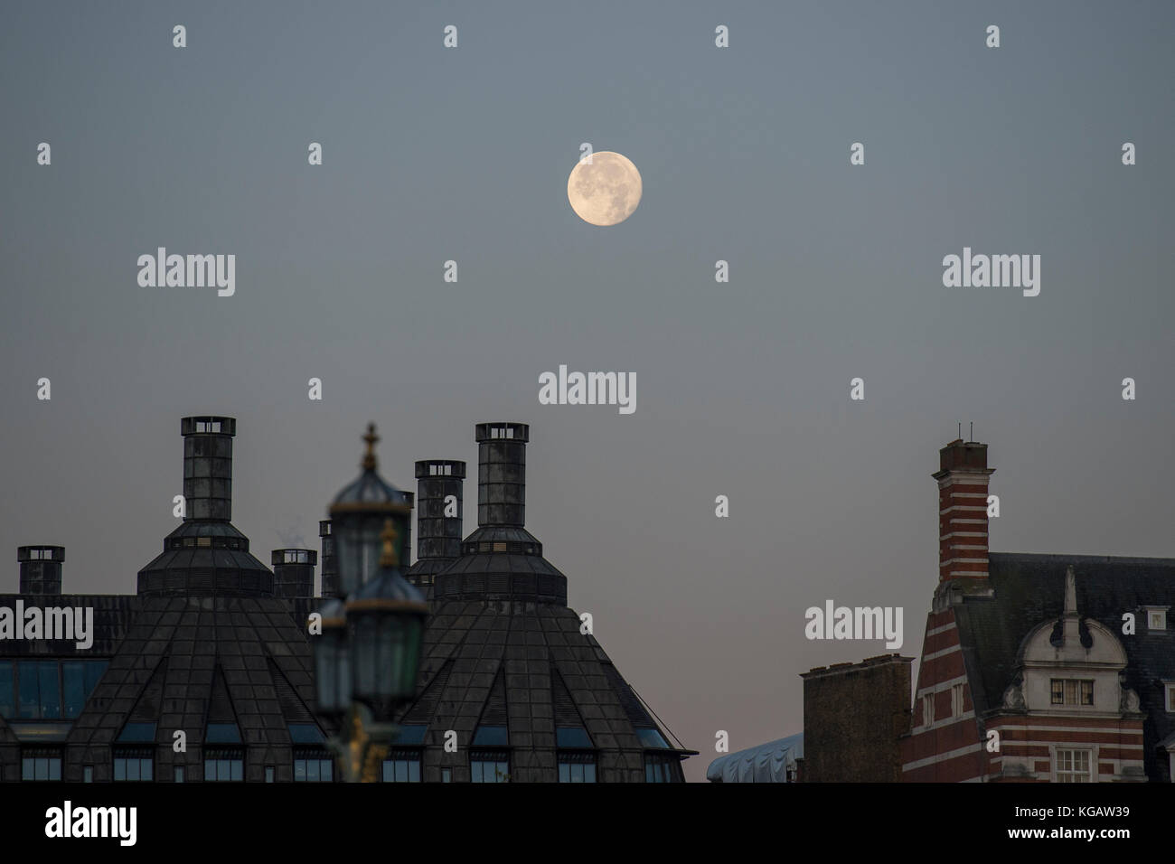 The moon above Portcullis House and Old Scotland Yard at sunrise in Autumn - Stock Image
