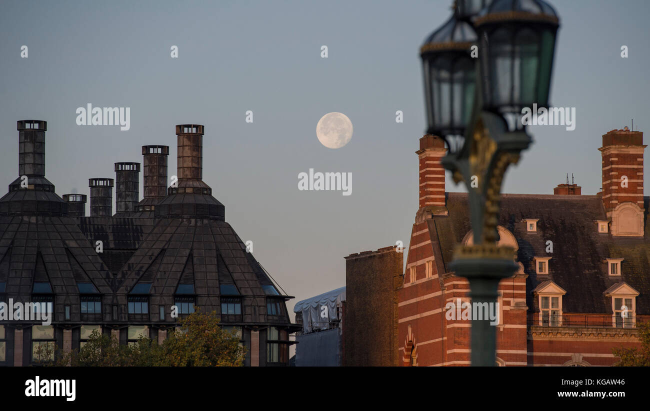 The moon between Portcullis House and Old Scotland Yard at sunrise in Autumn with street lamp on Westminster Bridge - Stock Image