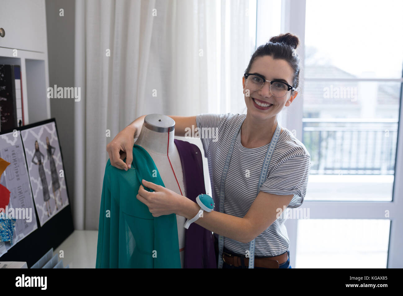 Fashion designer designing a fabric textile at home - Stock Image