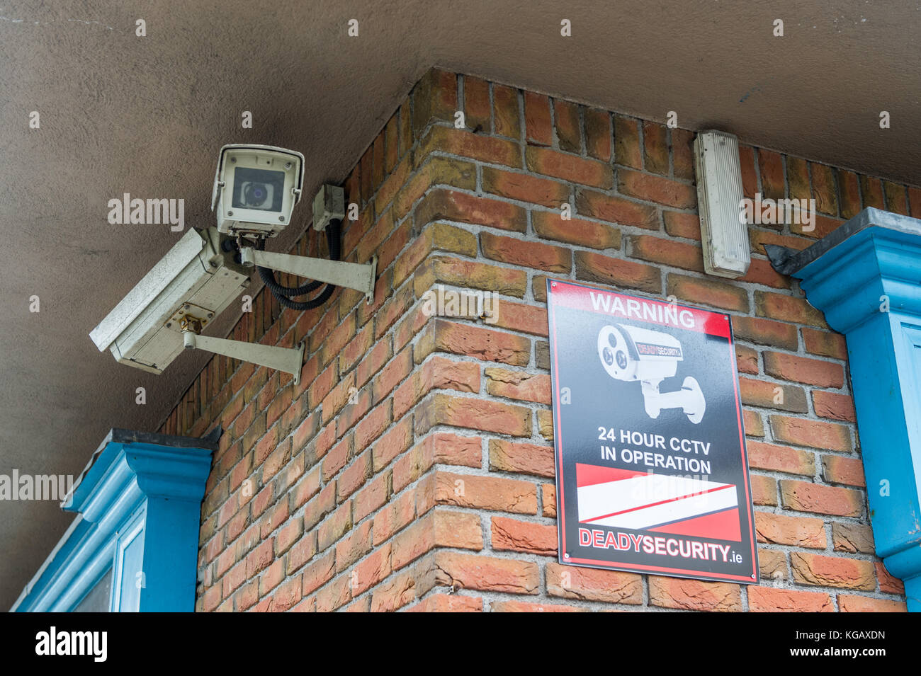 Two CCTV cameras on a brick wall facing in the opposite directions. - Stock Image