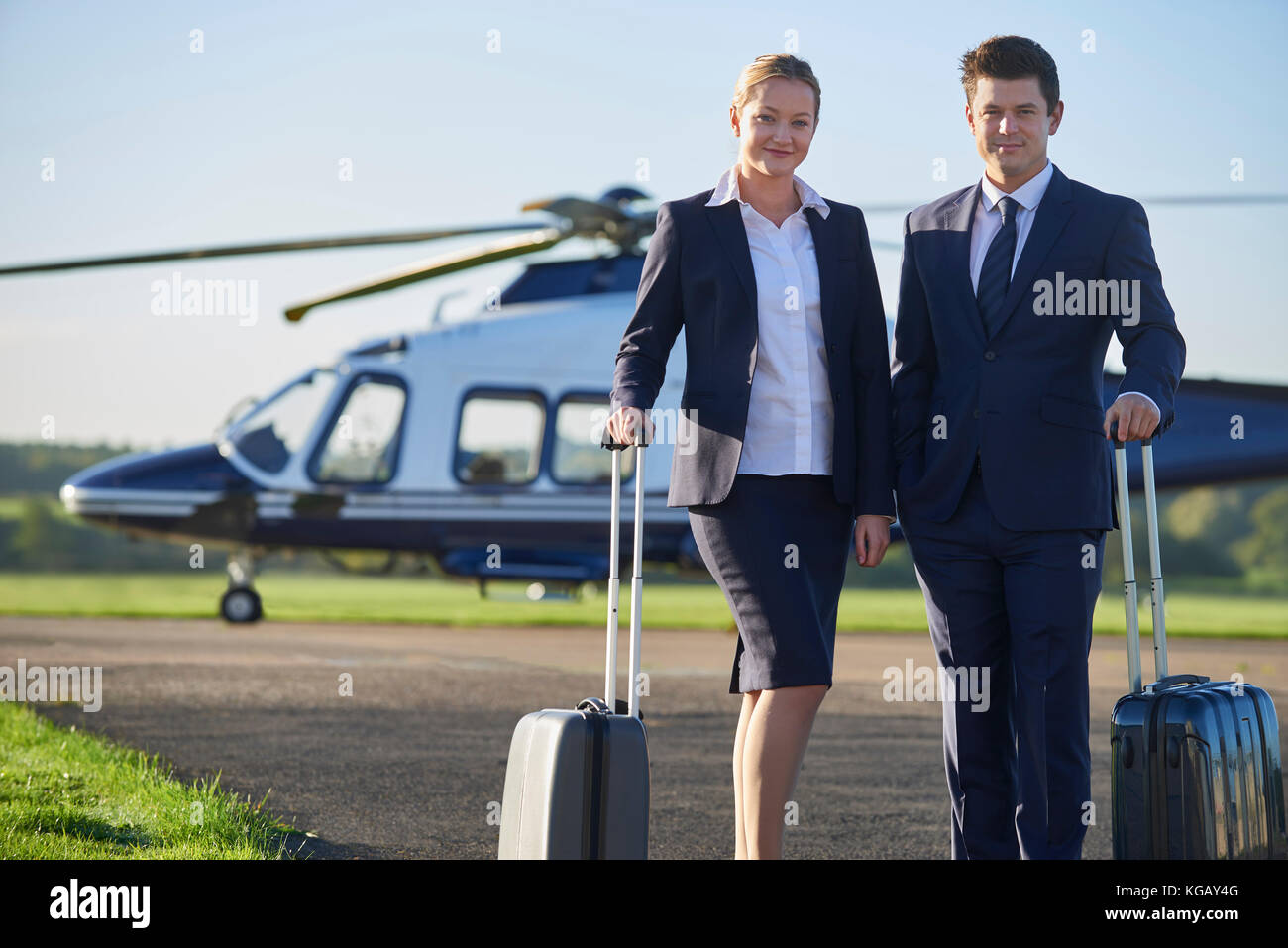 Portrait Of Businesswoman And Businessman Standing In Front Of Helicopter - Stock Image