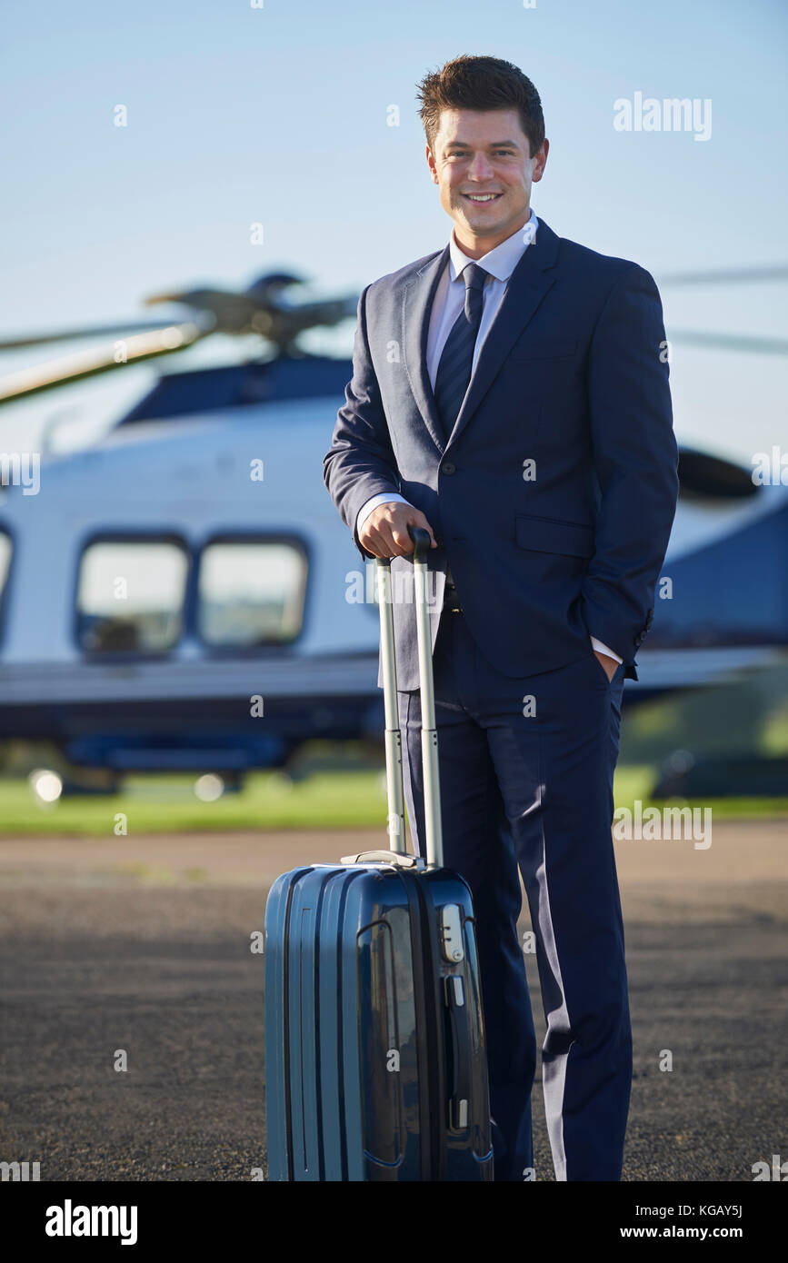 Portrait Of Businessman Standing In Front Of Helicopter - Stock Image