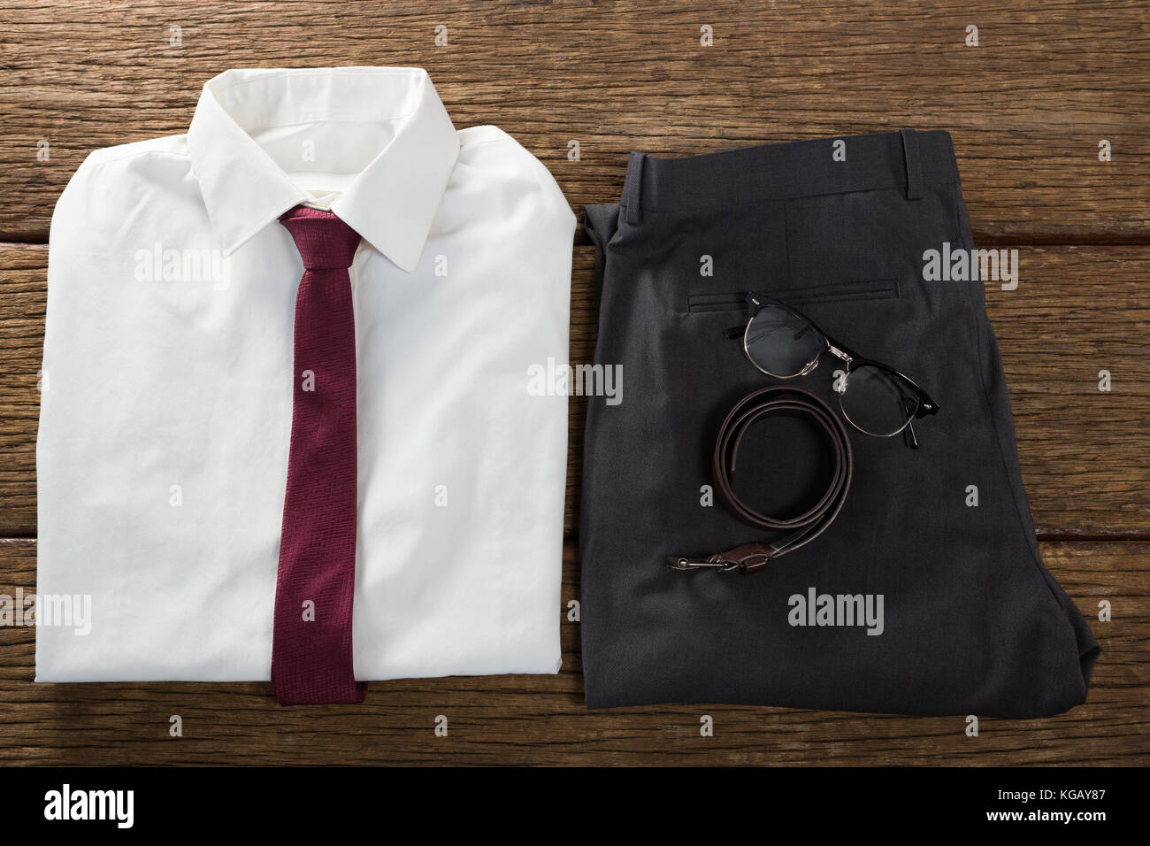 Close-up of folded school uniform, belt and spectacle on wooden plank - Stock Image