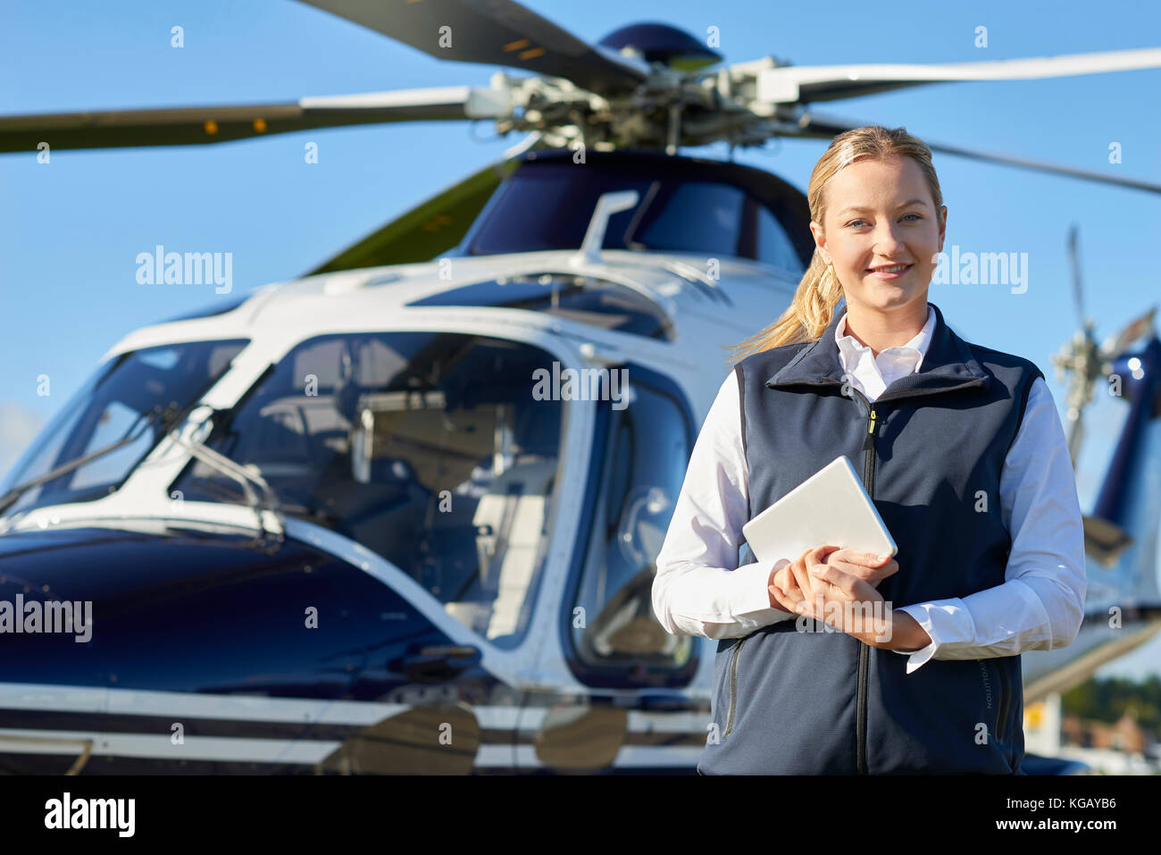 Portrait Of Female Pilot Standing In Front Of Helicopter With Digital Tablet - Stock Image