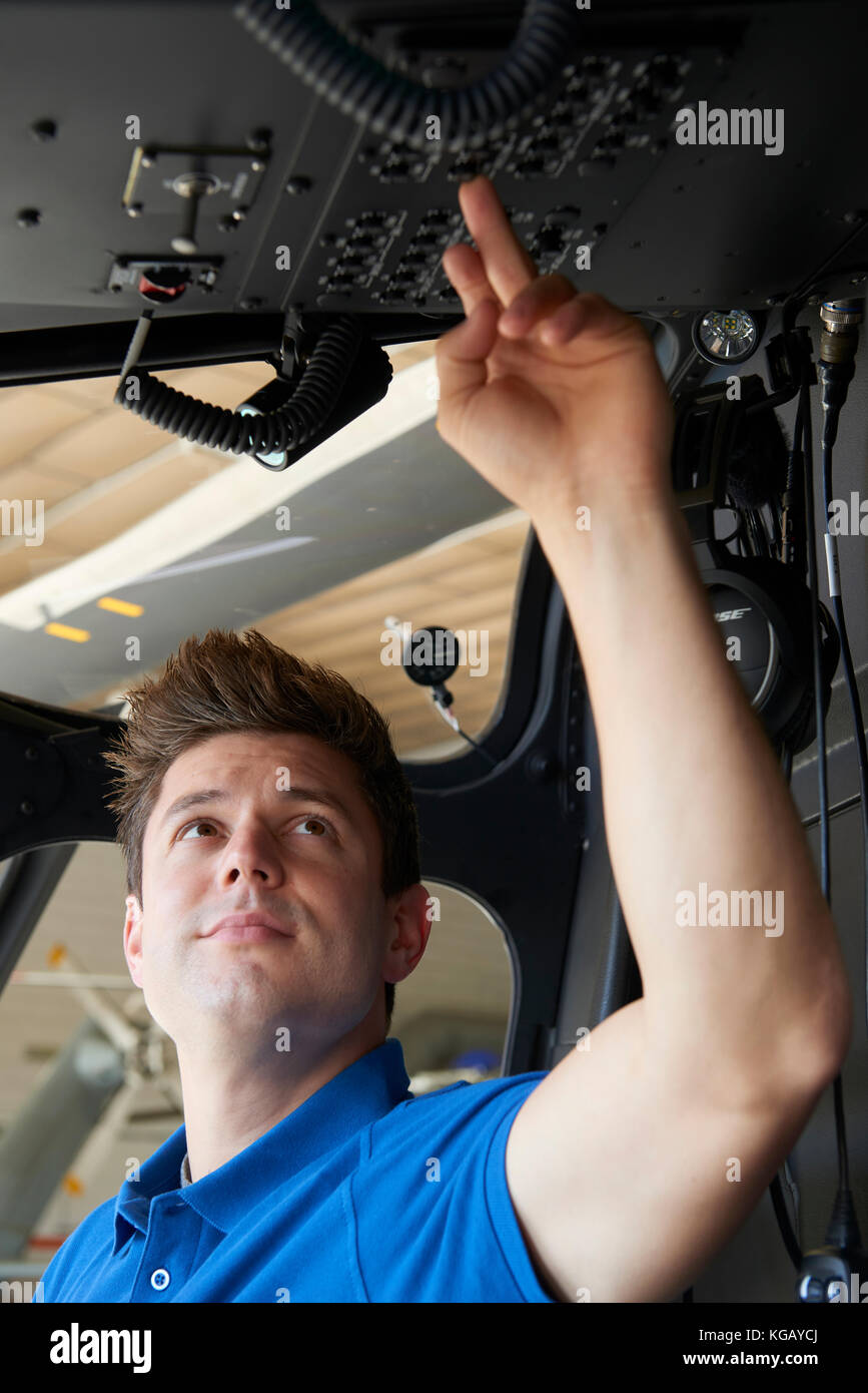 Male Aero Engineer Working In Helicopter Cockpit - Stock Image