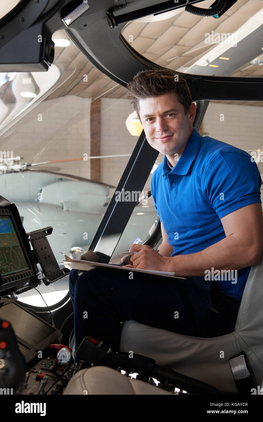 Portrait Of Male Aero Engineer With Clipboard Working In Helicopter Cockpit - Stock Image