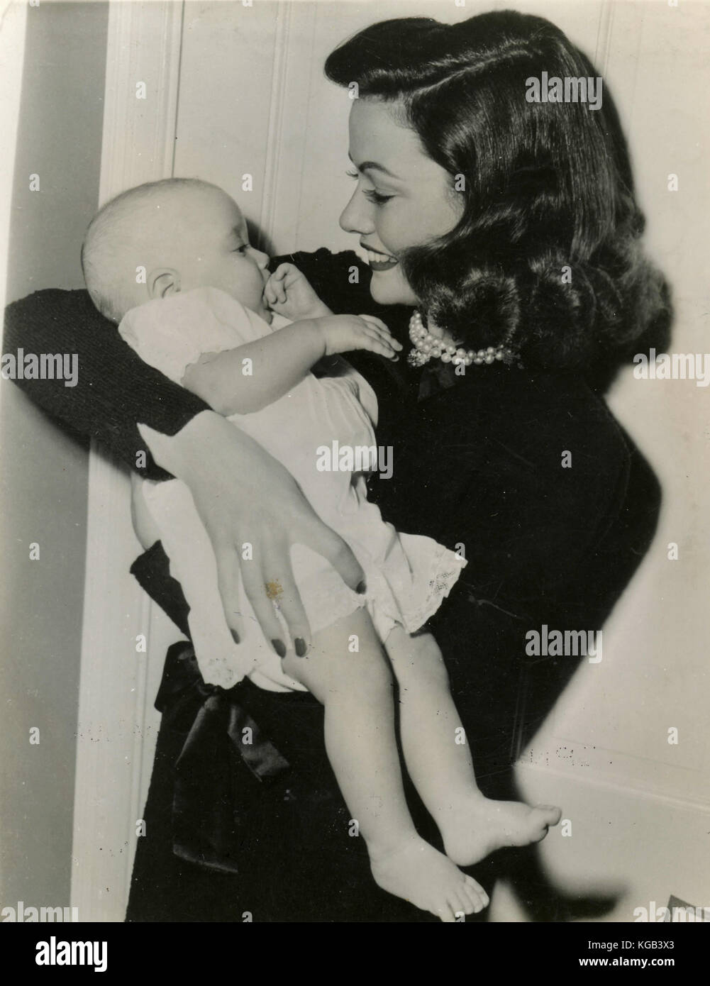 American actress Gene Tierney holding a baby - Stock Image