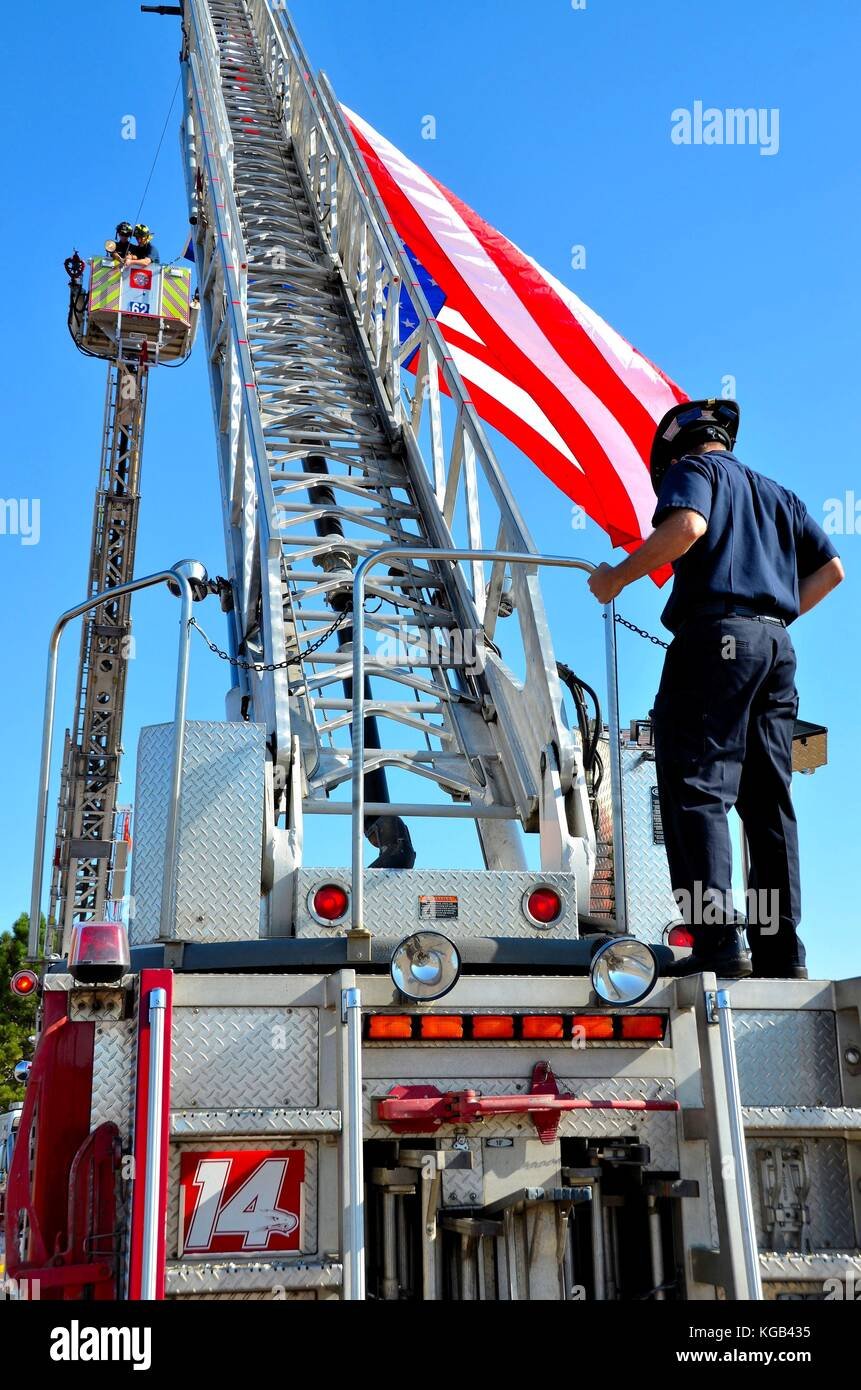 Firemen hanging an American Flag between their fire trucks - Stock Image