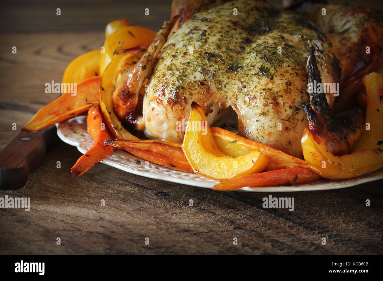Whole roasted chicken with fall vegetables - Stock Image