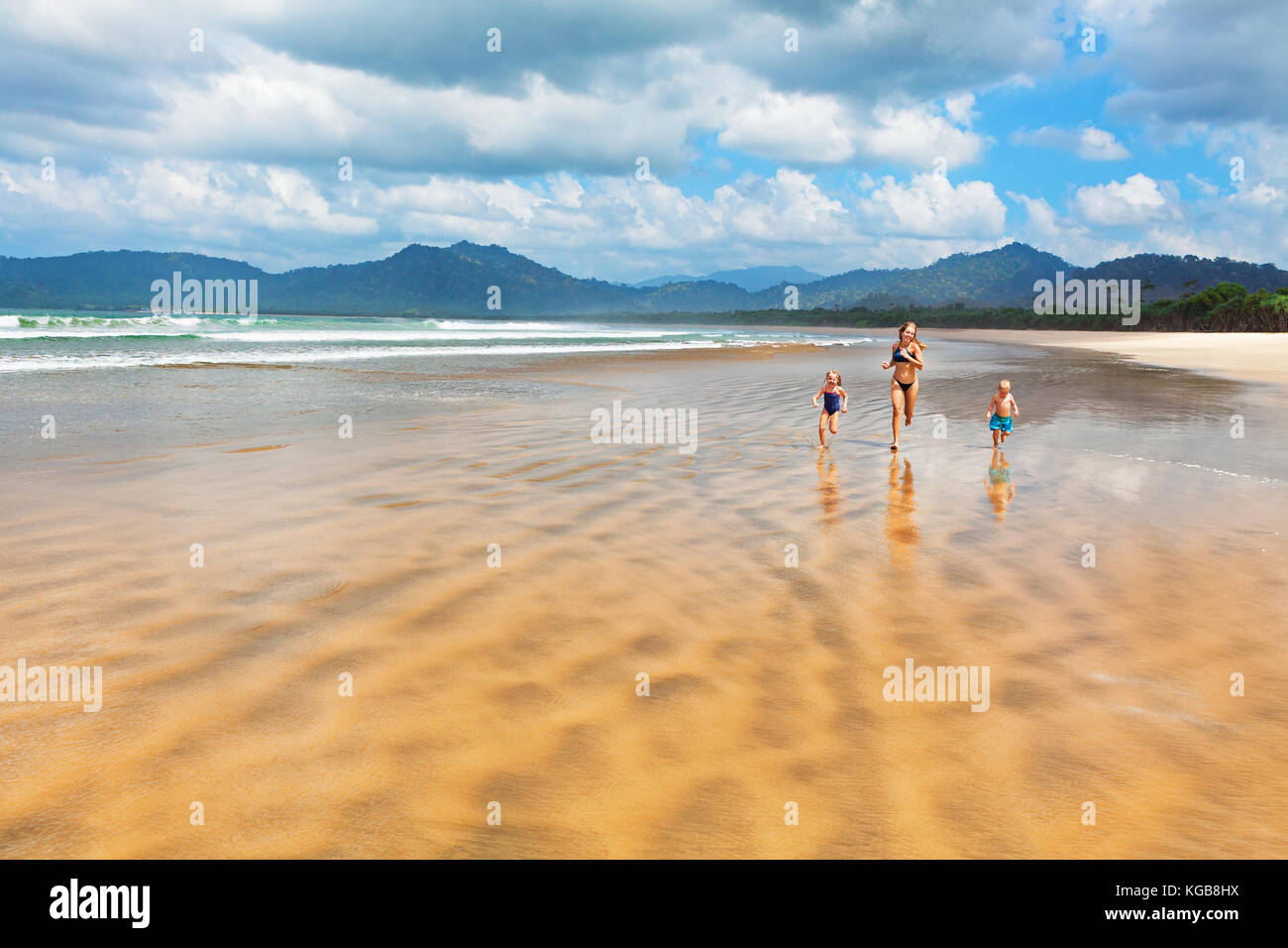 Happy family - mother, children have fun, run by water pool along sea surf on sand beach. Red island beach, pantai - Stock Image