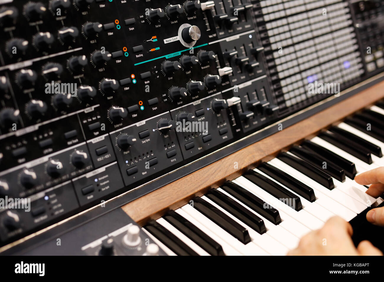 A musician at the keyboard of modern analog synthesizer. Selective focus. - Stock Image