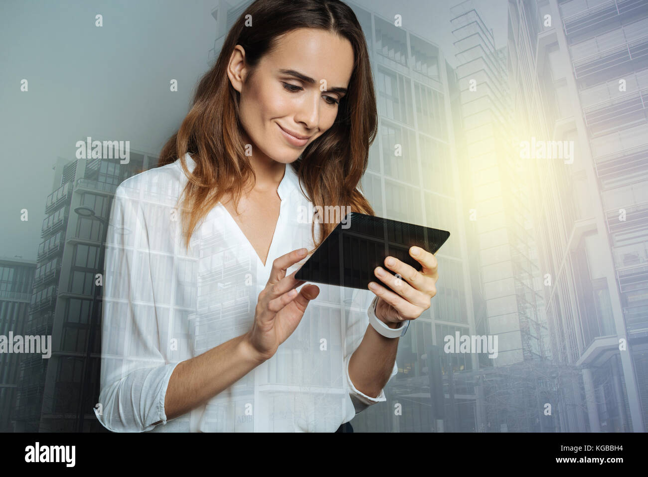 Cheerful pleasant woman browsing the Internet - Stock Image