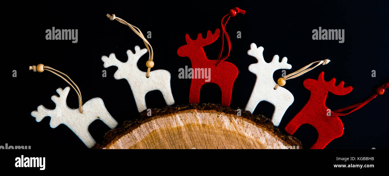 Red and white felt rein deers isolated on black. Christmas background with handmade ornaments - Stock Image