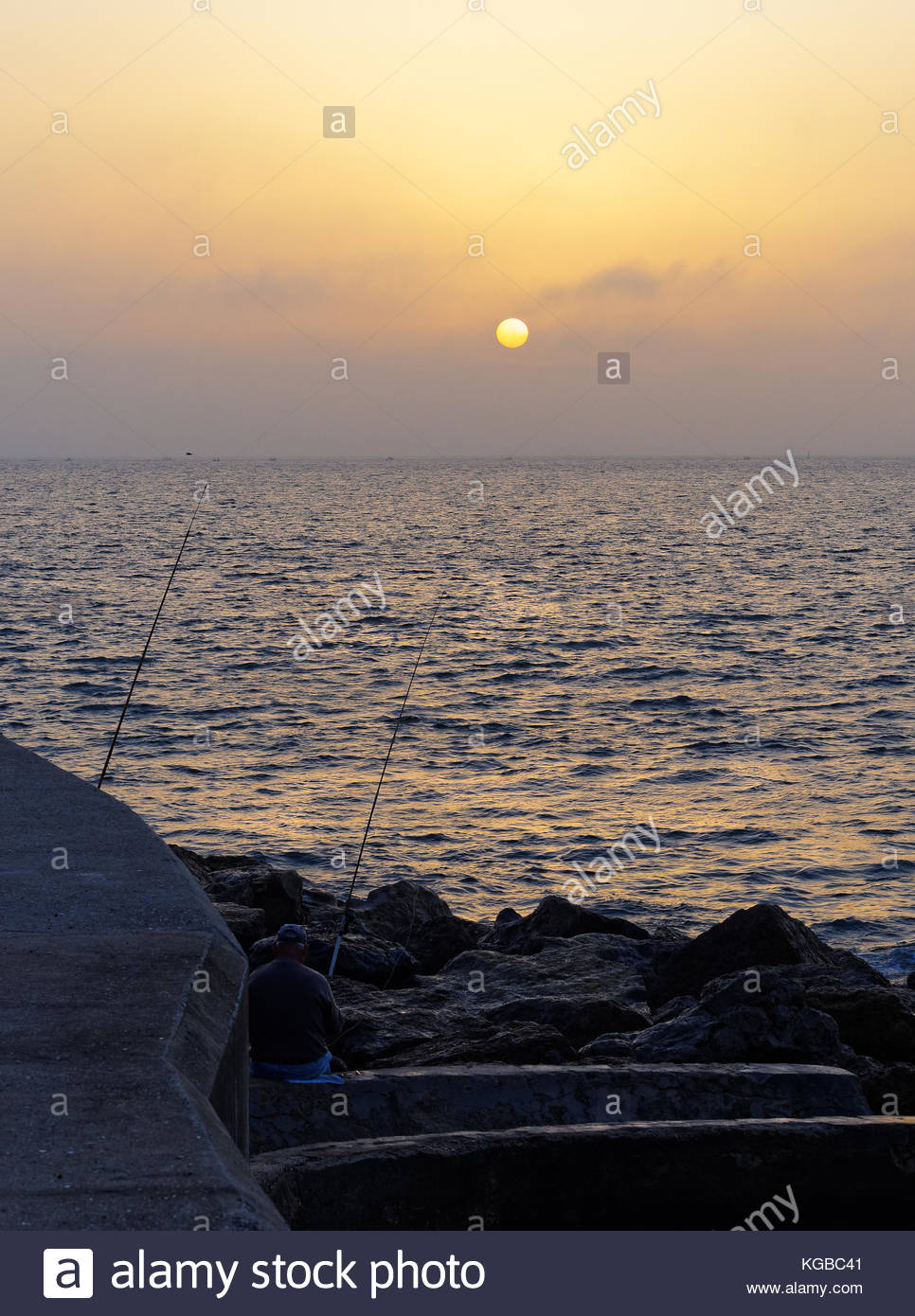 Fisherman on River Tagus shoreline, early morning sun with sea mist, Portugal - Stock Image