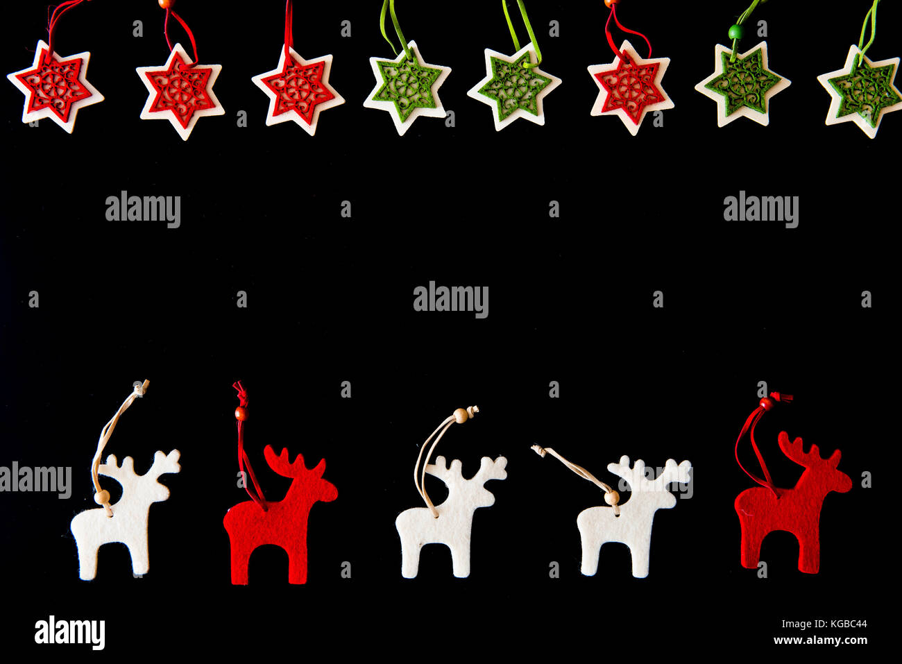 Felt rein deers iand snowflakes isolated on black. Christmas background with handmade ornaments - Stock Image