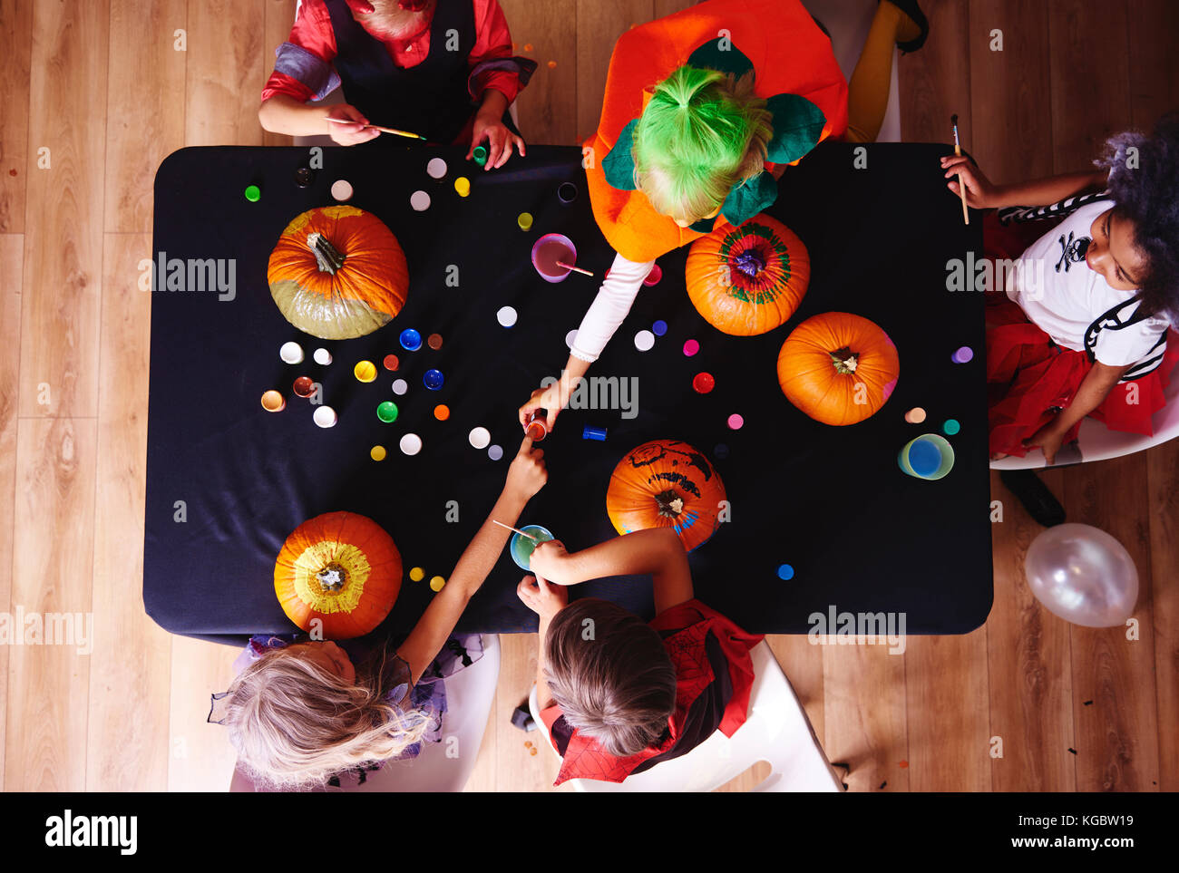 Kids in costume decorating a pumpkin - Stock Image