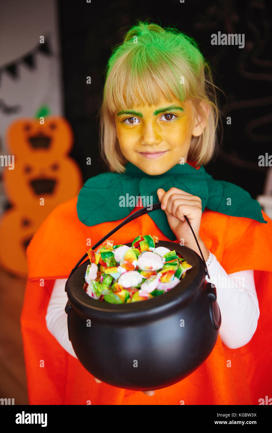Girl in pumpkin costume holding a bowl full of candies - Stock Image