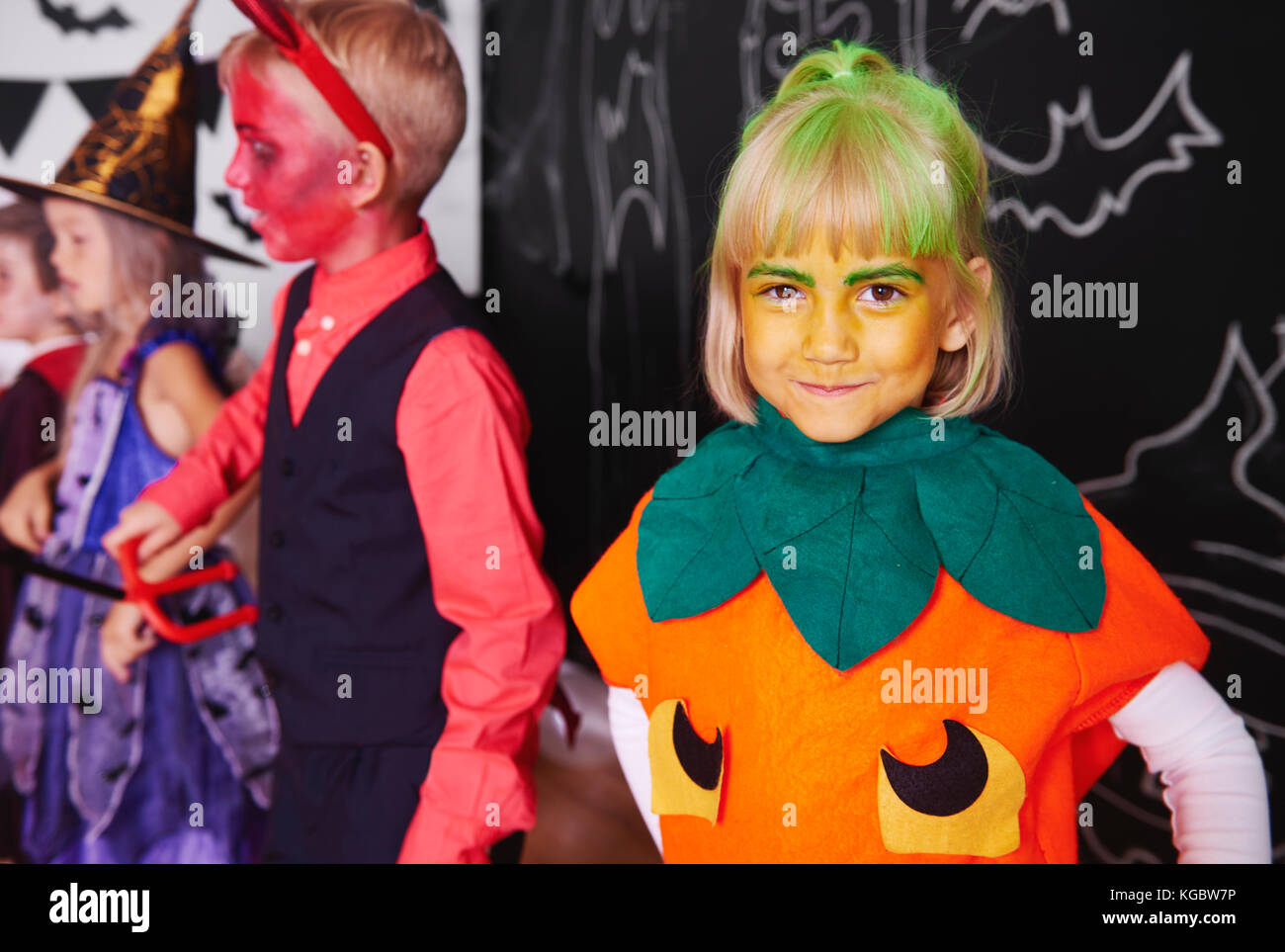 Cute girl in pumpkin costume celebrating halloween with friends  sc 1 st  Alamy & Cute girl in pumpkin costume celebrating halloween with friends ...
