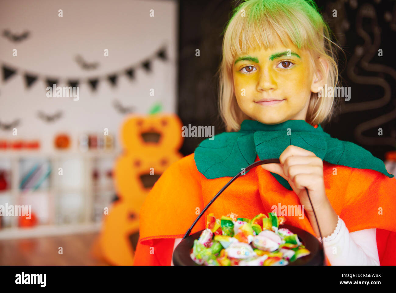 Girl in pumpkin costume with a bowl of candies - Stock Image
