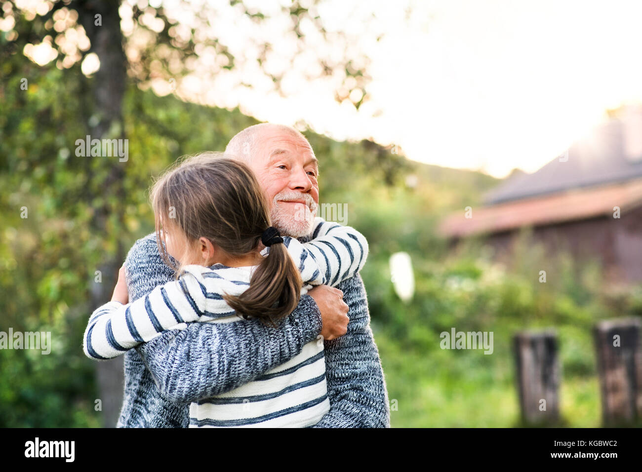 Grandfather giving his grandaughter a hug. - Stock Image