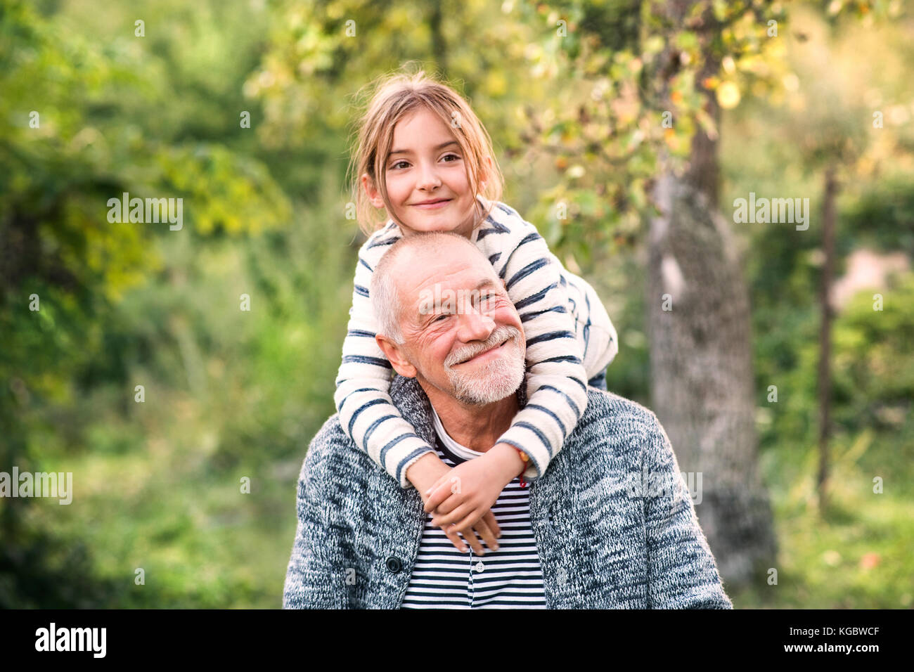 Grandfather carrying his grandaughter on his shoulders. - Stock Image