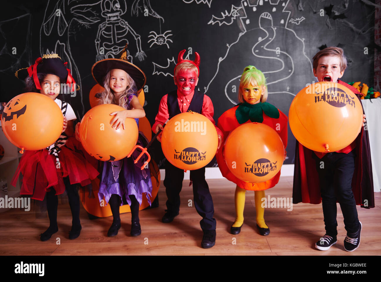Children in costume standing in a row and posing - Stock Image