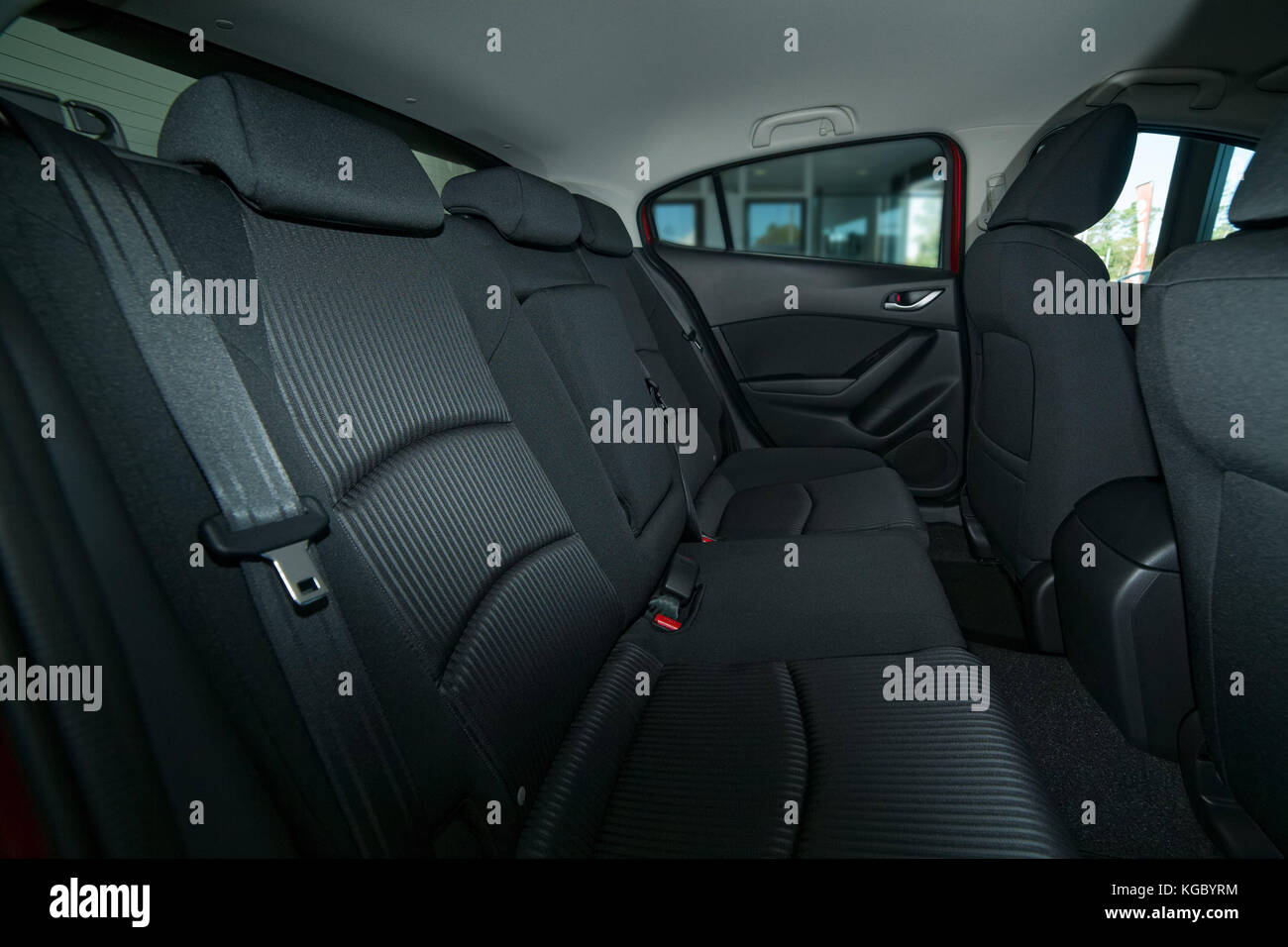 Modern car interior with back seat with seat belts, front seats and roof with a grab handle Stock Photo