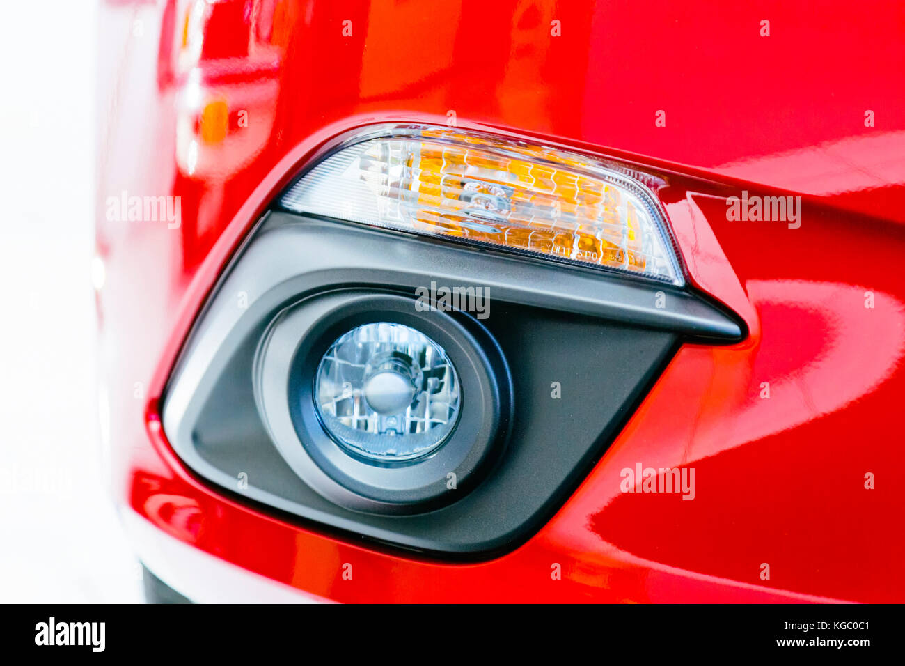 Car closeup with front daytime running lights and fog lights. Red shiny paint of a brand new modern auto vehicle - Stock Image