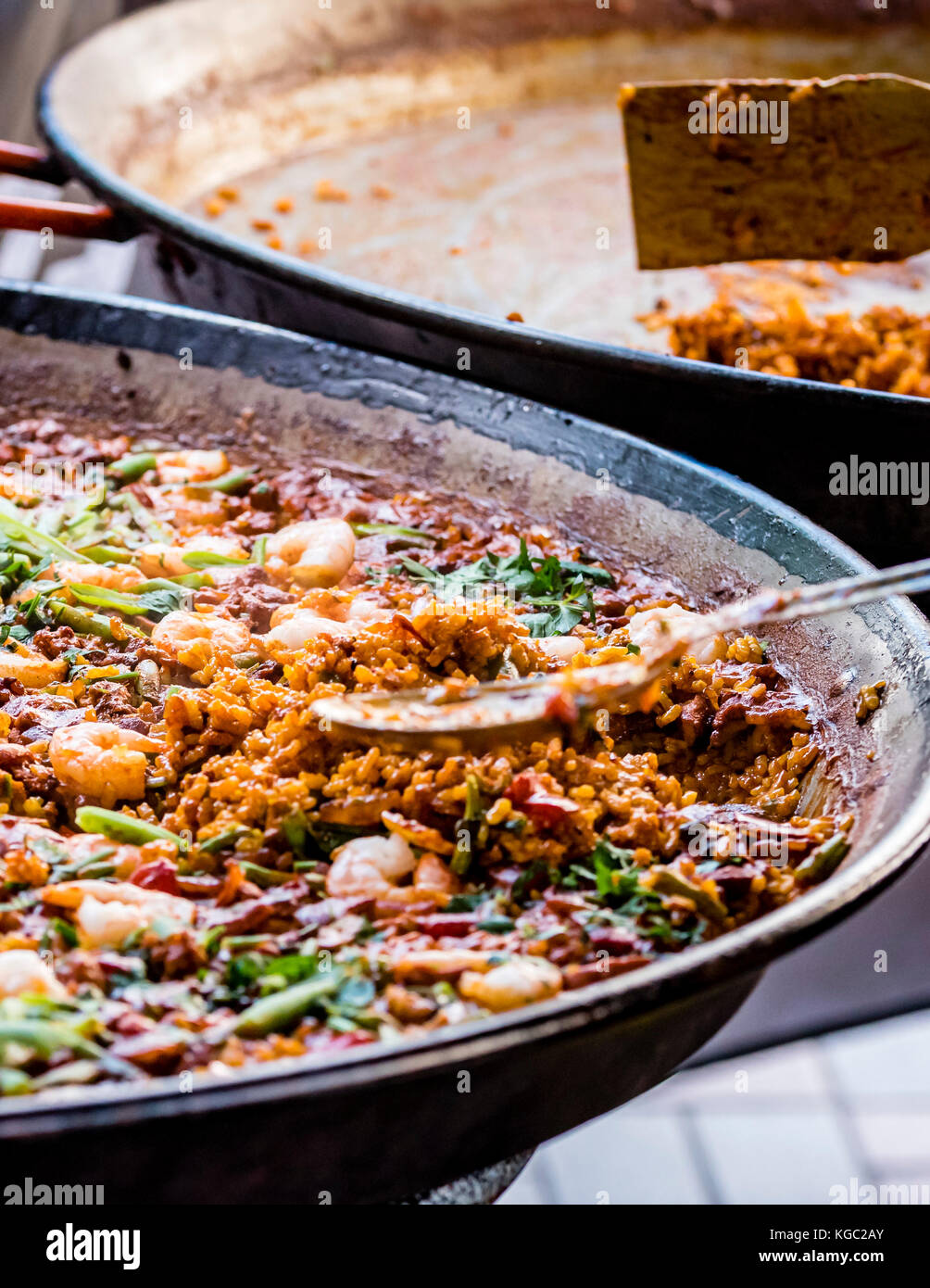 Paella dish with shrimp, closeup. Colorful Spanish paella rice in pan with vegetables and prawns. Empty pan in background Stock Photo