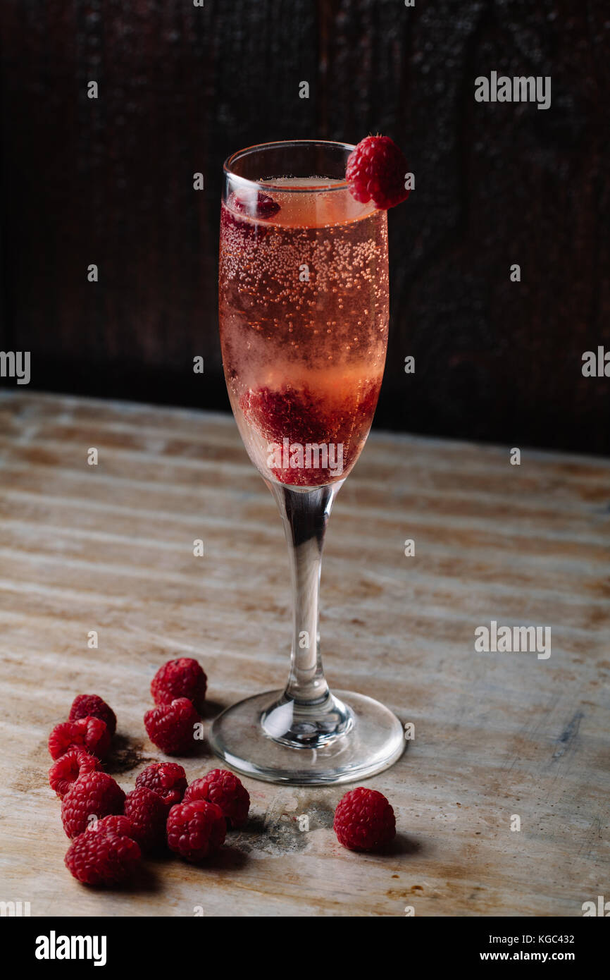 A glass of raspberry champagne on rustic background - Stock Image