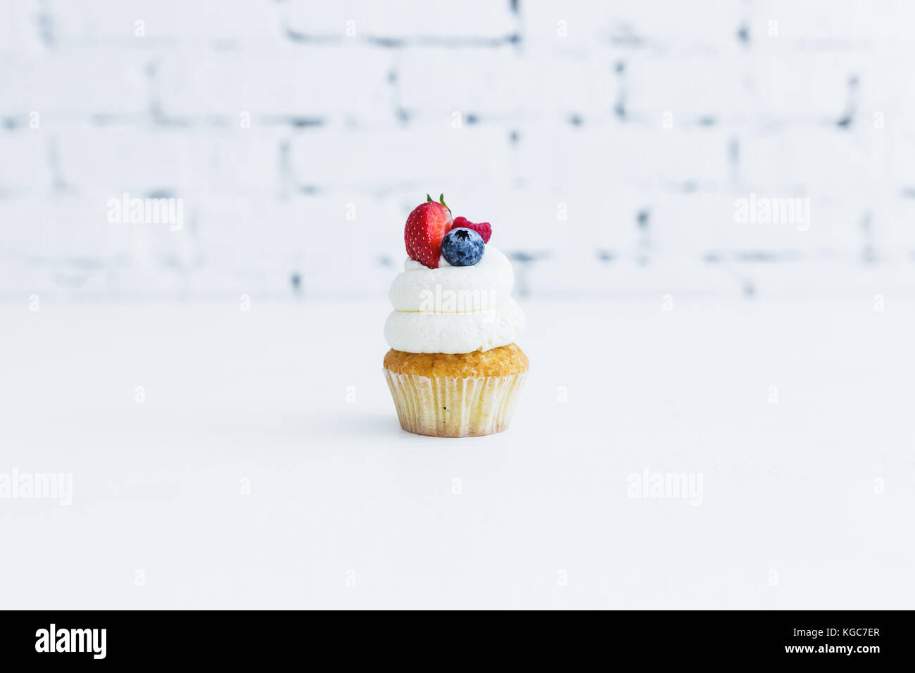Honey capcake with mascarpone cream with blueberry strawberries and raspberries. White background. - Stock Image