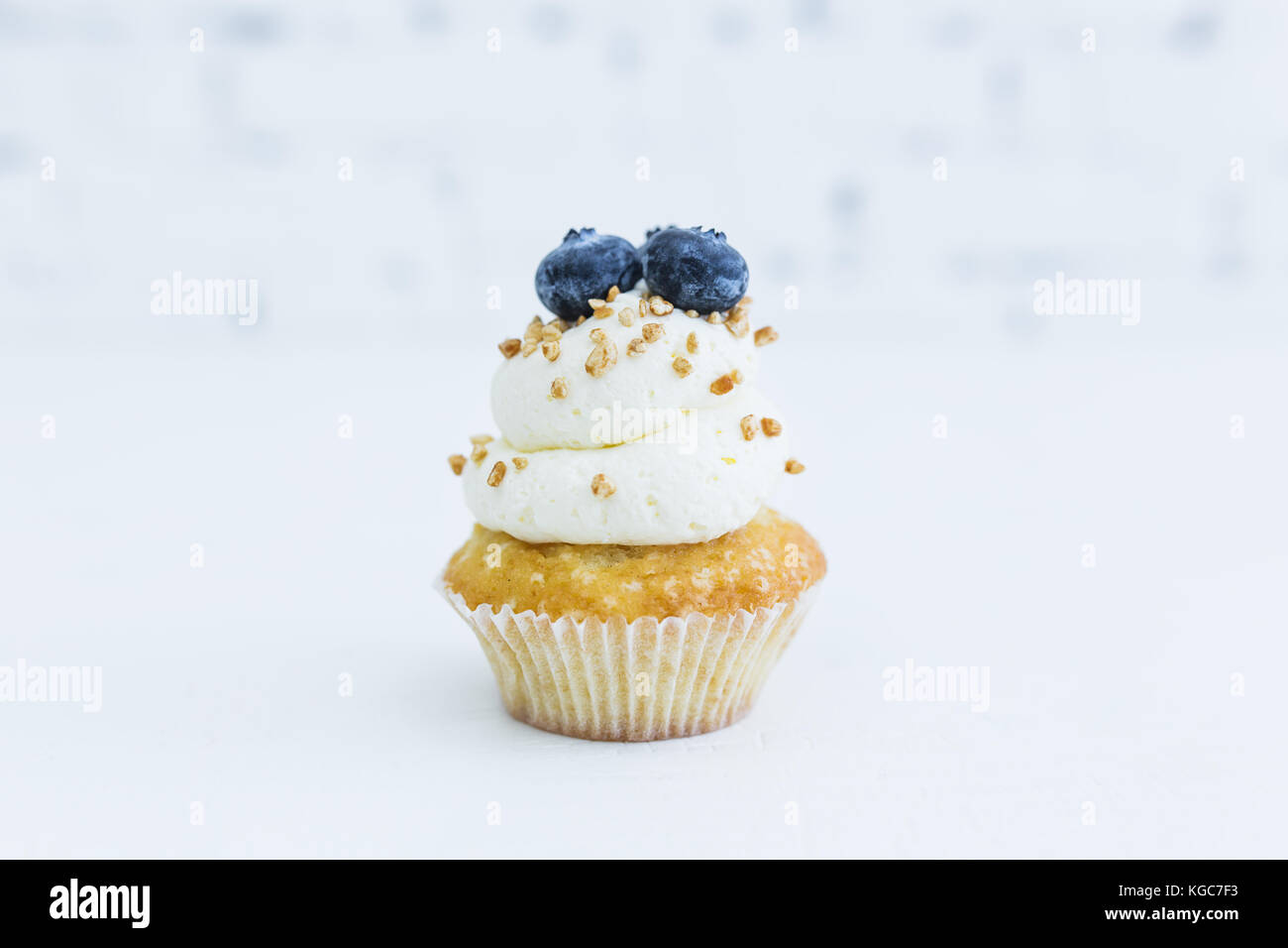 Honey capcake with mascarpone cream with blueberries and nuts. White background. - Stock Image