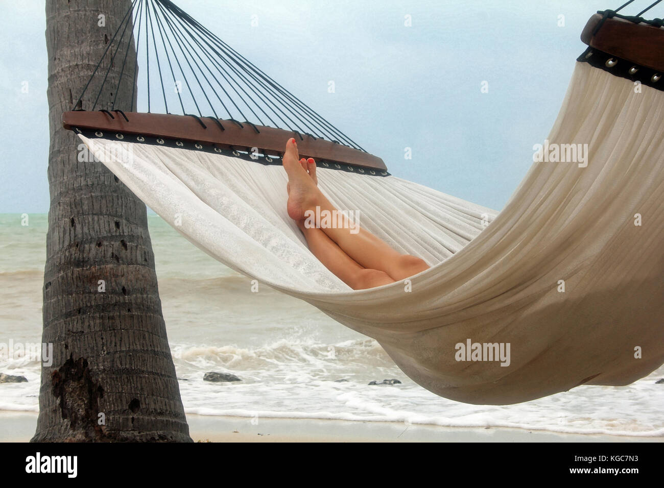 An air of mystery and relaxation is the mood of this shot of a woman relaxing in a hammock on a tropical beach underneath - Stock Image
