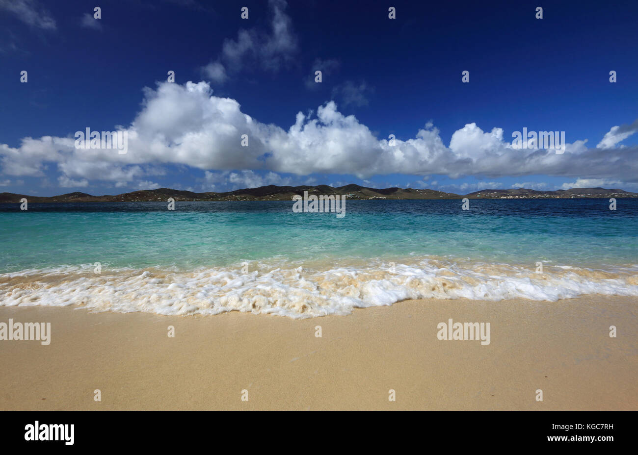 With the island of St. Croix off in the distance, gentle waves crash on the pristine shorelin of nearby Buck Island - Stock Image