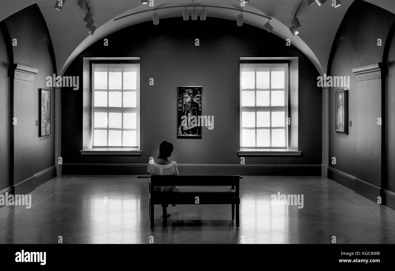 A woman sitting on a bench contemplating a painting at the museum in black and white.  She is alone with her thoughts. - Stock Image