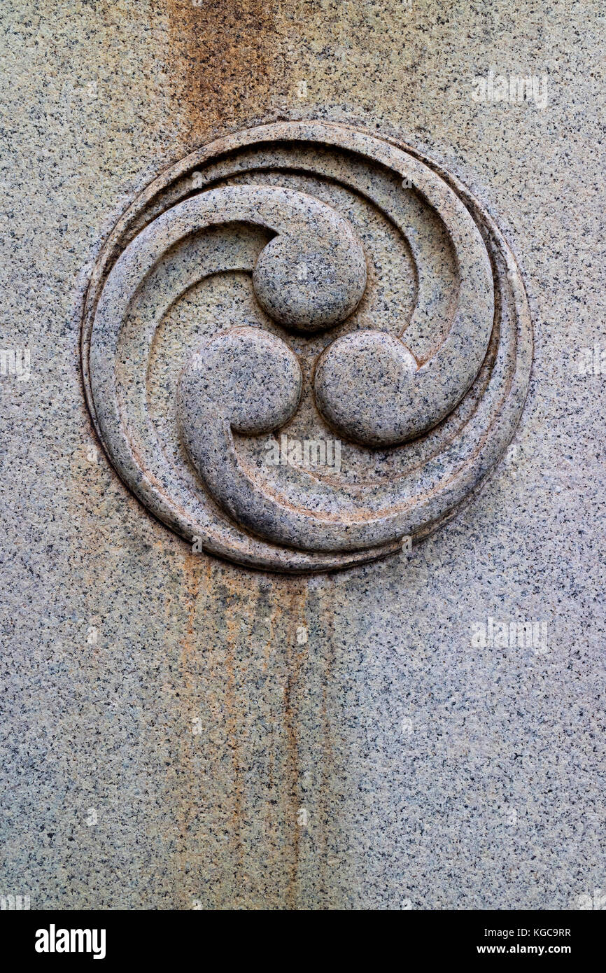 Japanese tomoe cut in stone as an emblem - Stock Image