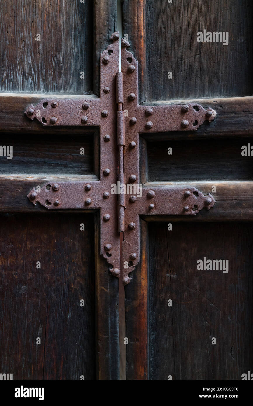Rusty iron hinge on a old wooden door - Stock Image