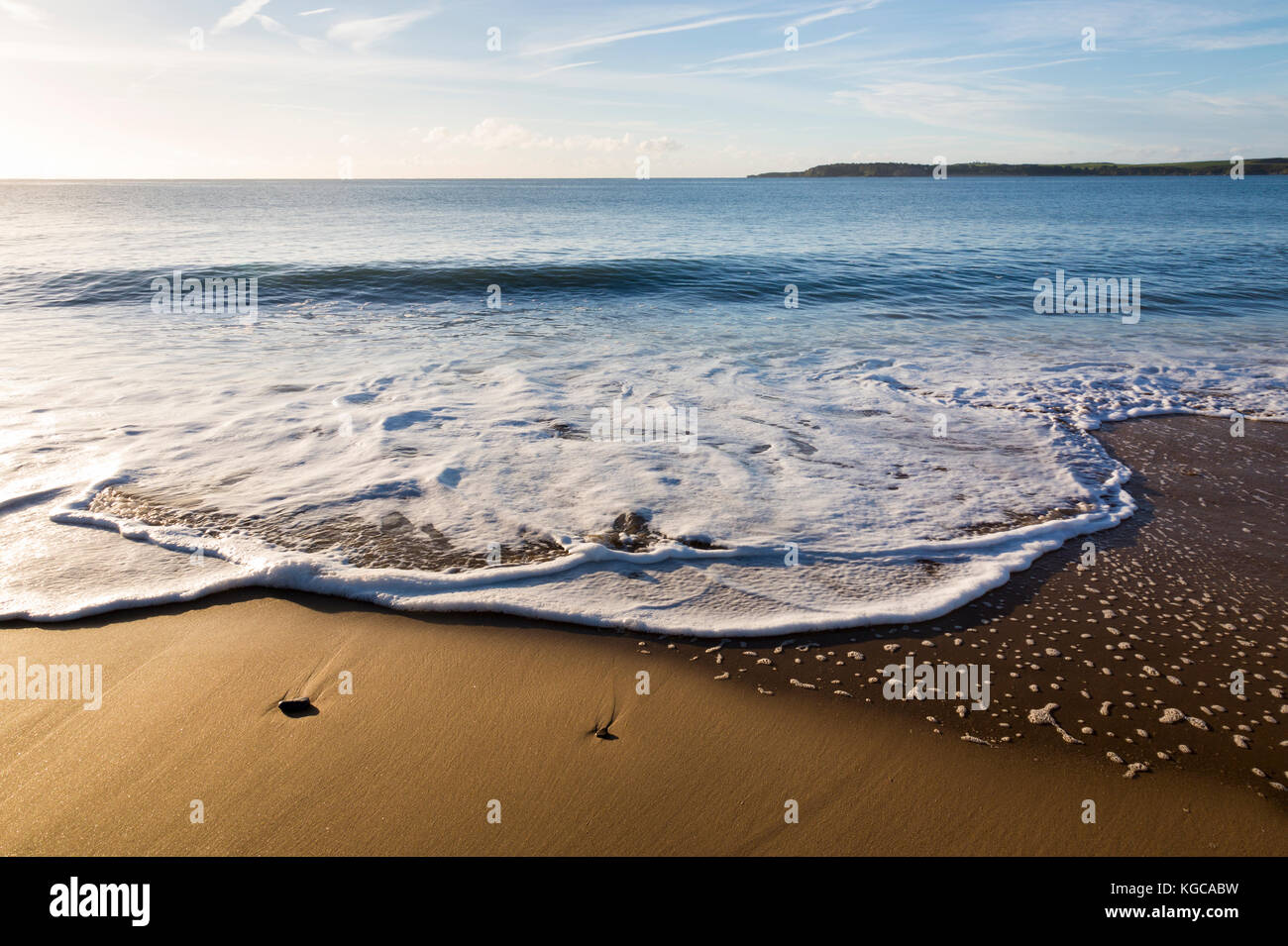 Gentle Surf Breaking on Tenby's South Beach in South Wales, UK - Stock Image