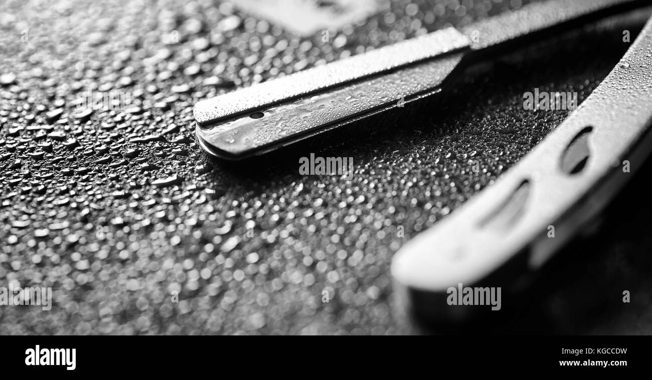A dangerous razor and a metal blade on the table. Men's shaving  - Stock Image