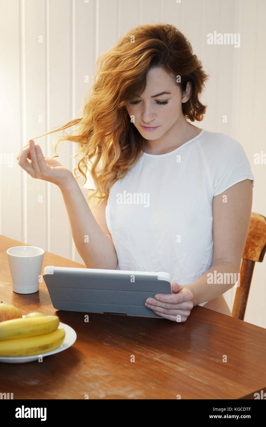 young woman using tablet computer at home - Stock Image
