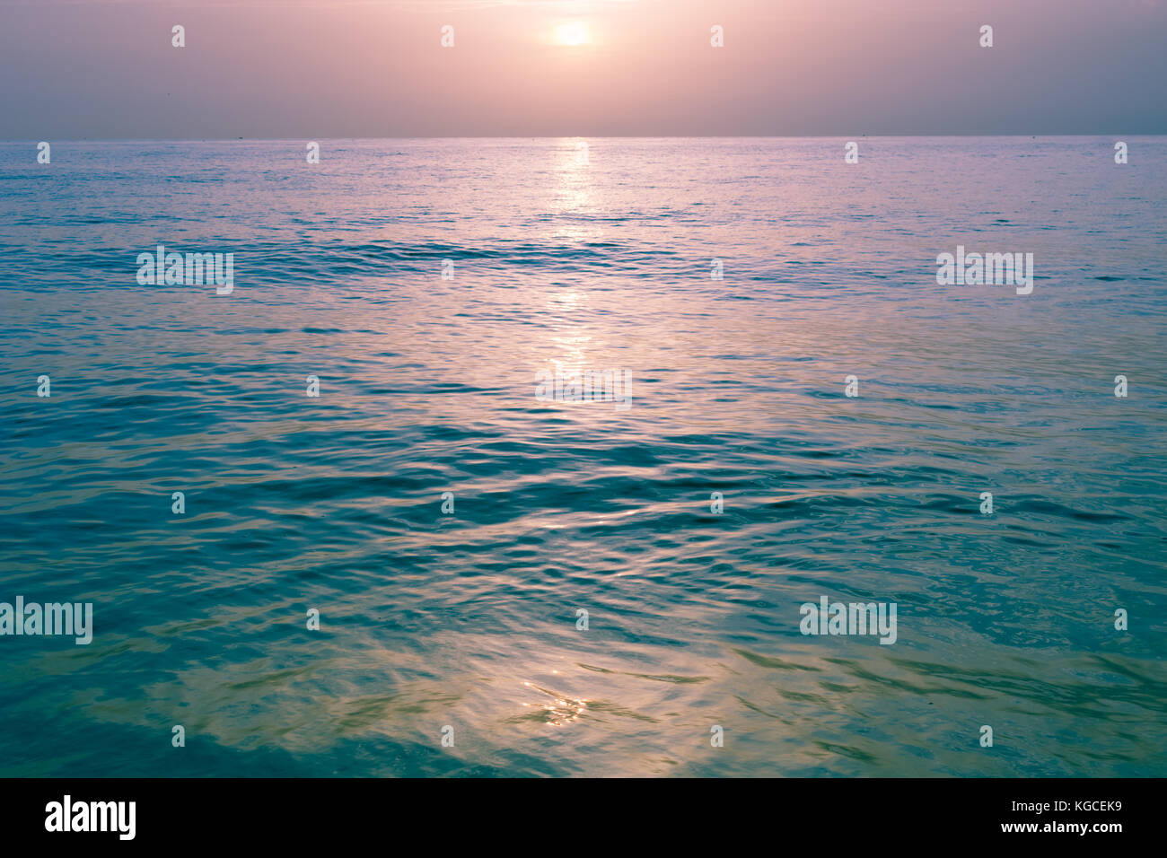 pastel colors in the sky and reflecting on the flat ocean water at sunrise - Stock Image
