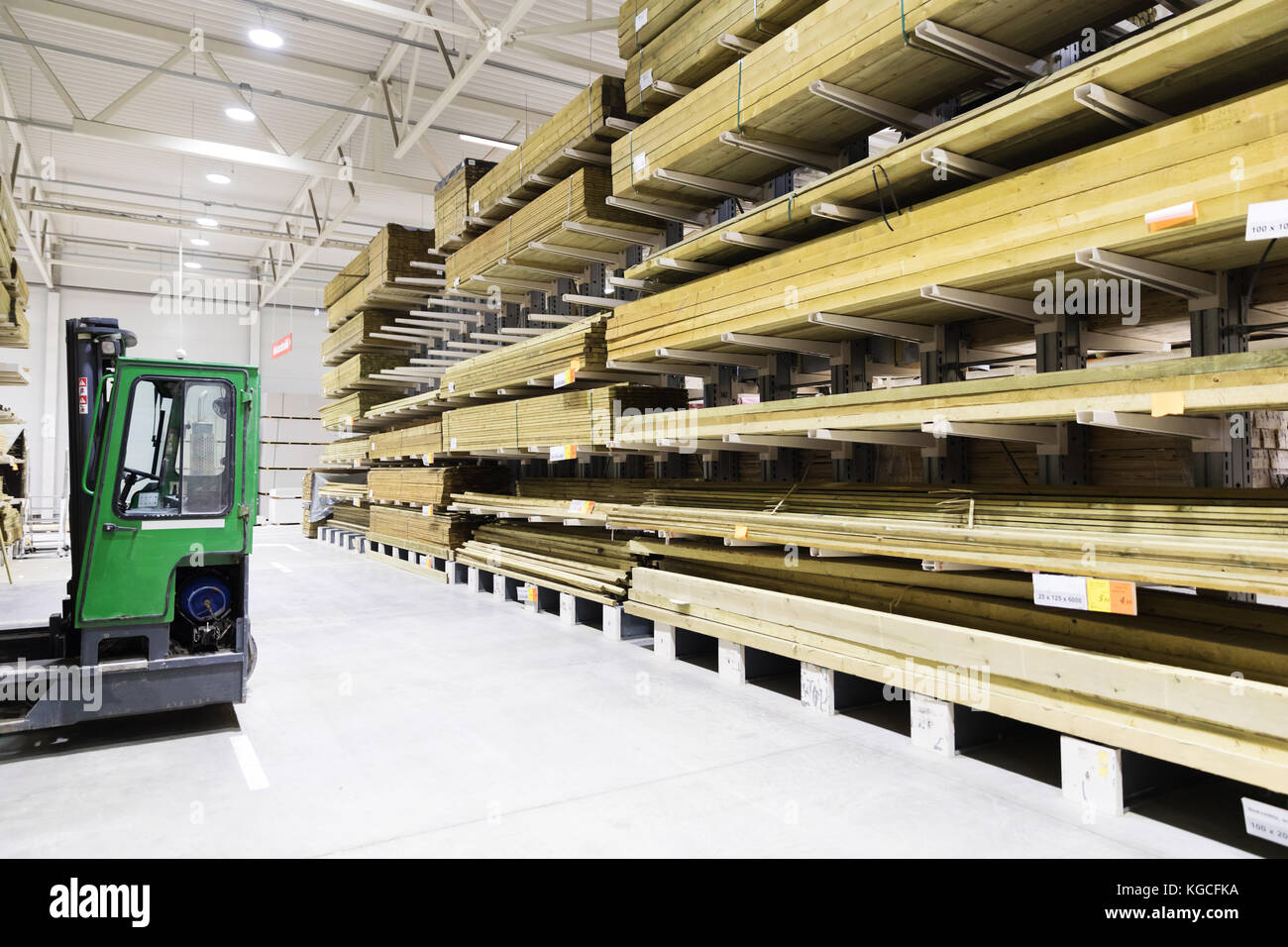 timber warehouse - shelves with wooden planks and forklift - Stock Image