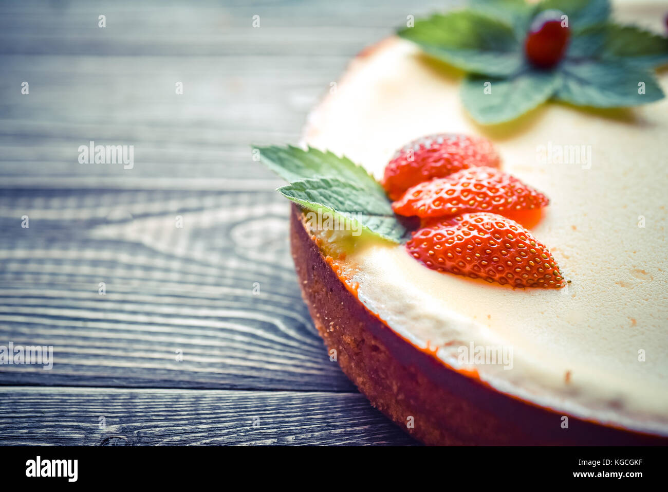 Fresh cheesecake with berries on a wooden background. Copy space - Stock Image