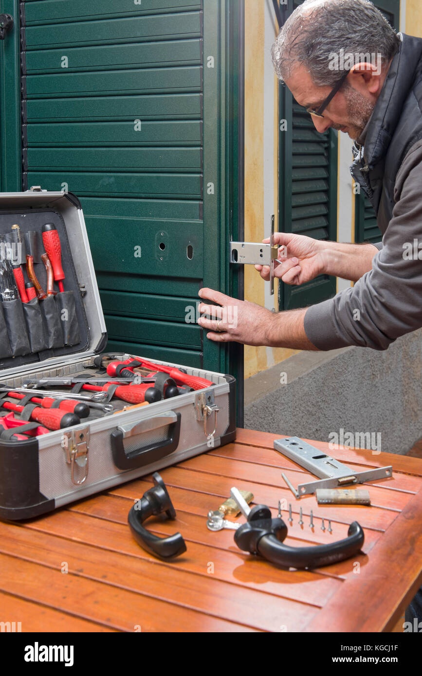 Locksmith repair a door lock replaces the lock. - Stock Image